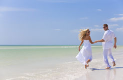 Junge Paar-Holding-Hände auf einem tropischen Strand Lizenzfreie Stockfotos