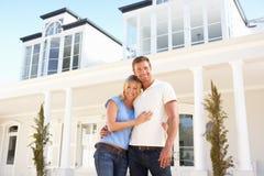 Junge Paar-stehendes äußeres Traumhaus Lizenzfreie Stockfotografie