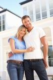 Junge Paar-stehendes äußeres Traumhaus Stockfotografie