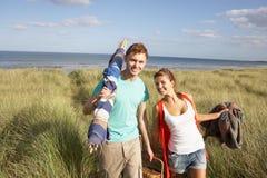 Junge Paar-tragender Picknick-Korb und Windschutz Lizenzfreie Stockfotos