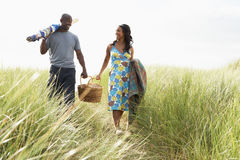 Junge Paar-tragender Picknick-Korb und Windschutz Lizenzfreie Stockfotografie
