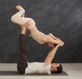 Junge Paare übendes acroyoga auf Matte zusammen Stockfotos