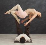 Junge Paare übendes acroyoga auf Matte zusammen Lizenzfreie Stockfotos