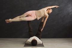 Junge Paare übendes acroyoga auf Matte zusammen Lizenzfreie Stockbilder