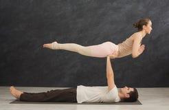 Junge Paare übendes acroyoga auf Matte zusammen Lizenzfreies Stockbild