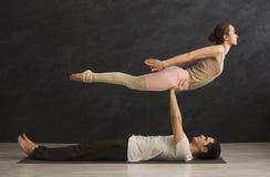 Junge Paare übendes acroyoga auf Matte zusammen Stockfoto