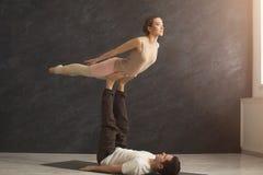 Junge Paare übendes acroyoga auf Matte zusammen Lizenzfreies Stockfoto