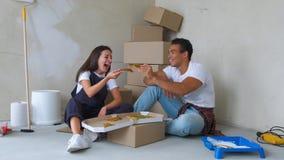 Junge Paare Appy, die Pizza während des repairment in der neuen Wohnung essen stock video