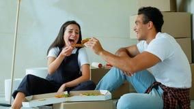 Junge Paare Appy, die Pizza während des repairment in der neuen Wohnung essen stock footage