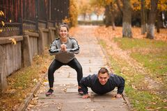 Junge Paare, Athleten, Zug im Herbstpark lizenzfreie stockfotos