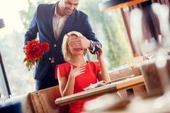 Junge Paare auf Datum in der Restaurantmannstellung hinter der sitzenden Frau, die ihre Augen machen Überraschungsholdingblumenst lizenzfreies stockfoto