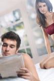 Junge Paare auf dem Bett im Schlafzimmer mit Zeitung Stockfotografie