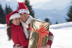 Junge Paare auf dem Schnee Stockfotos