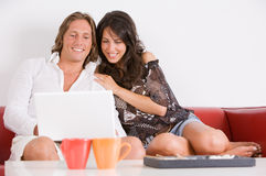 Junge Paare auf dem Sofa spielen mit dem Notizbuch Lizenzfreies Stockfoto