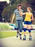 Junge Paare auf den Rollschuhen, die draußen reiten Stockfotos