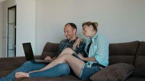 Junge Paare auf der Couch, die auf dem Laptop durch einen Videolink spricht stock video