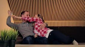 Junge Paare auf der Couch Die Frau nimmt die Fernsehdirektübertragung stock video footage
