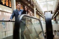 Junge Paare auf der Rolltreppe Stockbilder
