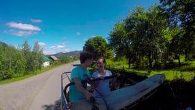 Junge Paare auf der Straße in einem Jeep mit einem offenen in den Bergen Der Kerl und das Mädchen reisen auf eine Aufnahme stock footage