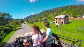 Junge Paare auf der Straße in einem Jeep mit einem offenen in den Bergen Der Kerl und das Mädchen reisen auf eine Aufnahme stock video footage
