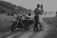 Junge Paare auf einem Motorrad auf dem Gebiet Lizenzfreie Stockfotos