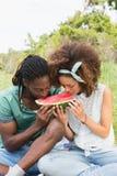 Junge Paare auf einem Picknick, das Wassermelone isst Stockfotografie