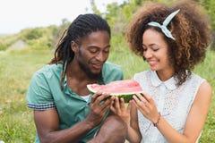 Junge Paare auf einem Picknick, das Wassermelone isst Lizenzfreie Stockbilder