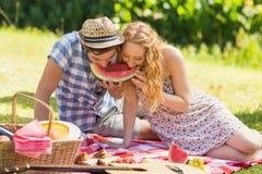 Junge Paare auf einem Picknick, das Wassermelone isst Stockfotos