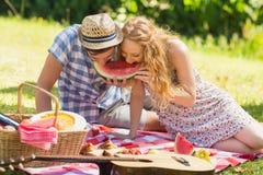Junge Paare auf einem Picknick, das Wassermelone isst Lizenzfreies Stockfoto