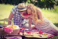 Junge Paare auf einem Picknick, das Wassermelone isst Stockbild