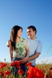 Junge Paare auf einem roten Mohnblumefeld Lizenzfreies Stockbild
