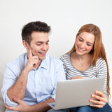 Junge Paare auf einem Sofa, das auf einem Notizbuch schaut Lizenzfreies Stockbild