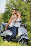 Junge Paare auf Motorrad/Roller auf Natur lizenzfreie stockfotos