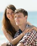 Junge Paare auf sandigem Strand Stockfotos