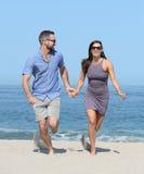 Junge Paare auf sandigem Strand Lizenzfreie Stockbilder