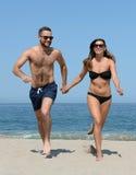 Junge Paare auf sandigem Strand Stockfoto