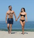 Junge Paare auf sandigem Strand Stockfotografie