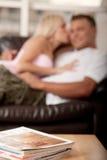Junge Paare auf Sofa Stockbilder