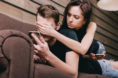 Junge Paare auf Sofa mit Handy Lizenzfreies Stockbild
