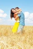 Junge Paare auf sonnigem Feld des Weizens Stockbild
