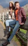 Junge Paare auf Zaun in den Bergen Lizenzfreie Stockbilder