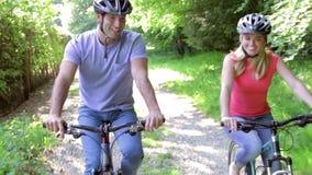 Junge Paare auf Zyklus-Fahrt in der Landschaft stock footage