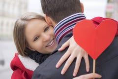 Junge Paare beim Liebesumarmen Freundin, die rote Herz und das Lächeln hält Roter heart-shaped Schmucksachegeschenkkasten und ein Stockfotos