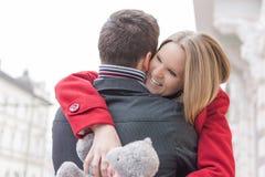 Junge Paare beim Liebesumarmen Freundin, die Teddy Bear und das Lächeln hält Liebes- und Valentinsgrußtageskonzept Lizenzfreie Stockfotos