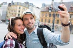 Junge Paare an den Feiertagen selfie nehmend Stockfotos