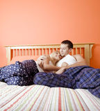 Junge Paare in den Pyjamas, die auf Bett sitzen Lizenzfreies Stockfoto