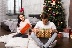 Junge Paare in den Pyjamas, die ihre Geschenke beim an sitzen auspacken Stockfotografie