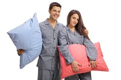 Junge Paare in den Pyjamas, die Kissen halten und das camer betrachten Stockbild