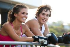 Junge Paare in den Verpacken-Handschuhen, die auf Geländer sich lehnen Stockfotos