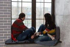 Junge Paare in den warmen gestrickten Strickjacken, die heraus das Fenster während schauen Stockfotografie